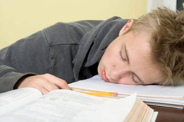 Foto di un bambino che dorme a scuola. Immagine di accompagnamento all'articolo Prevenzione bambini: i controlli medici consigliati per il ritorno a scuola.