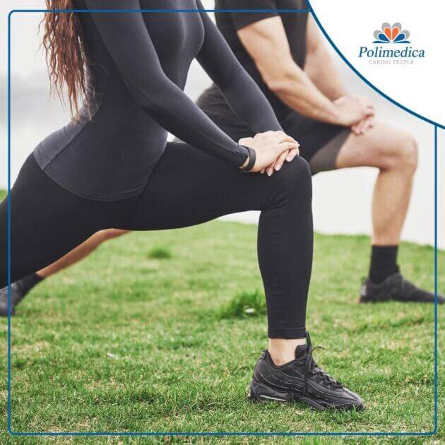 Foto, con logo di Polimedica Melfi, di due sportivi che eseguono degli esercizi di stretching su un prato. Immagine di accompagnamento all'articolo dedicato a Esercizi di stretching.