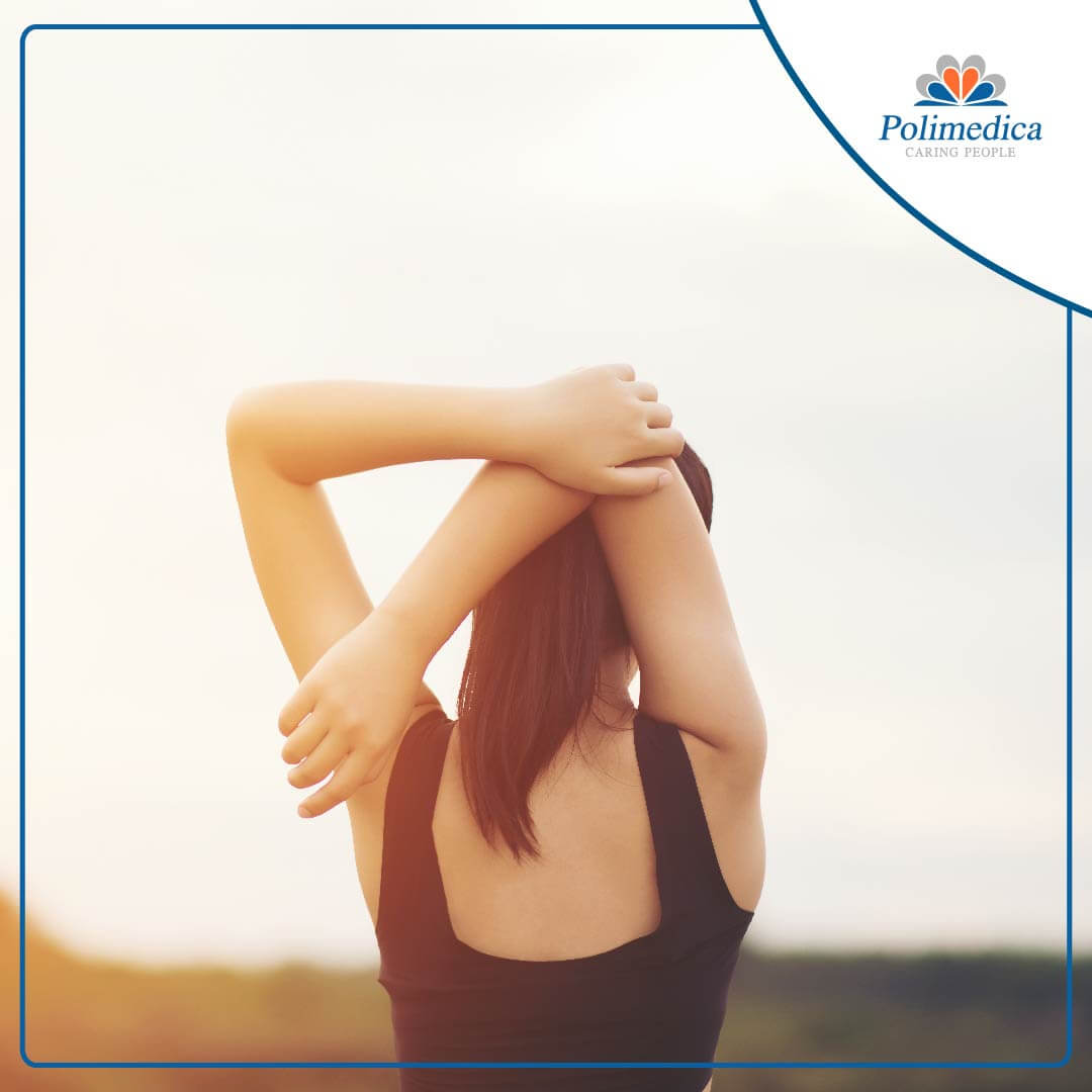 Immagine, con logo di Polimedica Melfi, di una donna di spalle che esegue degli esercizi di stretching. Foto di accompagnamento all'articolo dedicato a Esercizi di stretching.