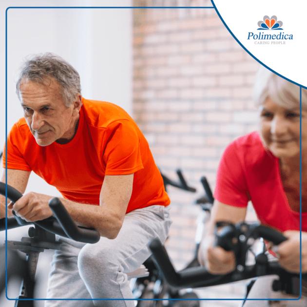 """Immagine, con logo di Polimedica Melfi, di due anziani che svolgono attività fisica su delle cyclette. Foto di accompagnamento all'articolo dedicato a """"La riabilitazione cardiologica fisioterapica""""."""