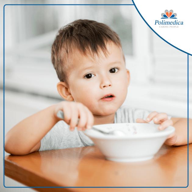 """Foto, con logo di Polimedica Melfi, di un bambino che mangia seduto ad un tavolo. Immagine di accompagnamento all'articolo dedicato a """"Celiachia in età pediatrica""""."""