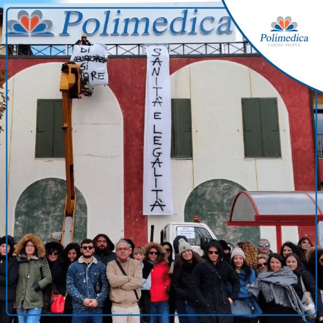 """Immagine, con logo di Polimedica Melfi, di un gruppo di lavoratori del poliambulatorio durante un sit-in dedicato a """"Sanità e legalità"""". Foto utilizzata per la pagina Difendiamo Polimedica."""